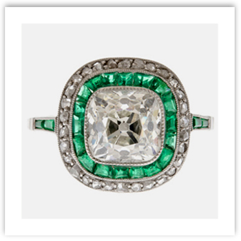 Cushion cut diamond surrounded by emeralds
